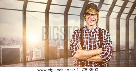 Smiling blond hipster crossing arms against room with large window looking on city