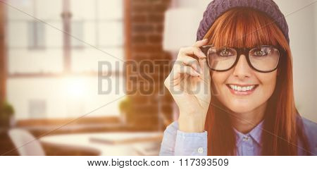 Smiling hipster woman looking at camera against laptop on desk with glasses and notepad