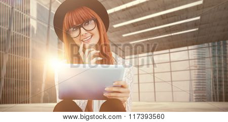 Smiling hipster woman using her tablet against modern room overlooking city