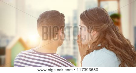 Woman whispering secret to boyfriend against view of a business desk
