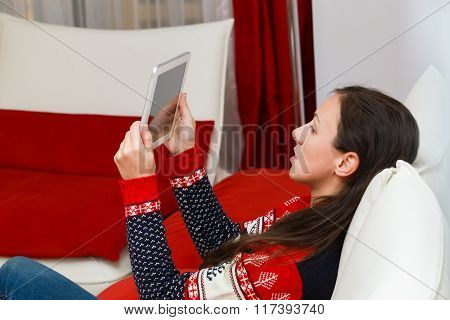Young Woman In Modern Interior Living Room Looks At Tablet