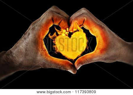 Couple making heart shape with hands against black