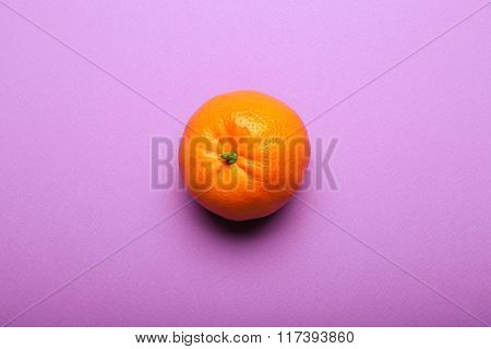 One Tangerine On Bright Purple Background