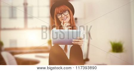 Smiling hipster woman using her tablet against laptop on desk with glasses and notepad