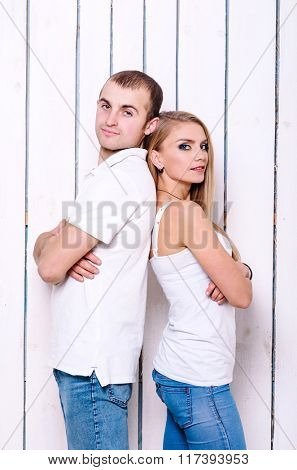 Beautiful and happy couple. On the background white wooden pattern.