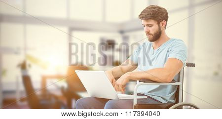 Man in wheelchair using computer against board room