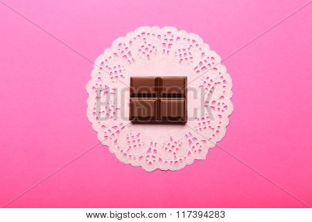 Chocolate Piece And Napkin On Pink Background