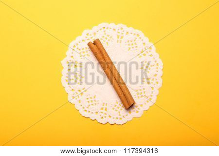 One Stick Cinnamon With Napkin On Yellow Background