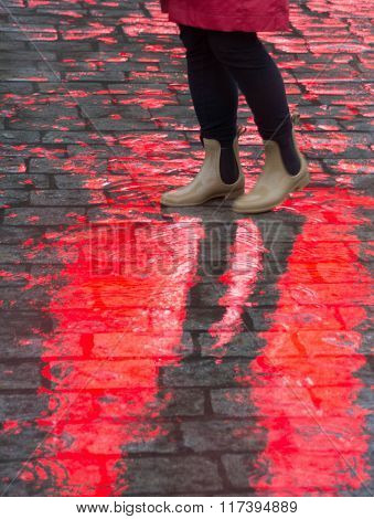 Feet on city cobblestones with red reflection from an advertising poster