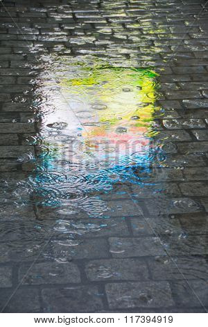 Reflection of different colors from an advertising board on cobblestones on a rainy evening.