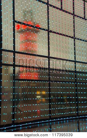 Reflection of a modern lighted tower in a big window with lights and frames
