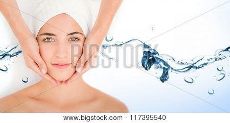 Water bubbling on white surface against attractive woman receiving facial massage at spa center