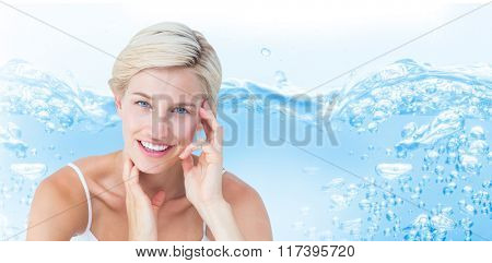 Happy woman smiling at camera against close up on blue sparkling water