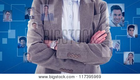 Happy businesswoman standing arms crossed against blue background