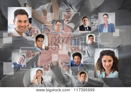 Smiling business team standing in circle hands together against grey vignette