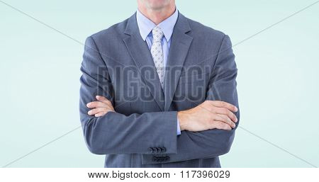 Portrait of smiling businessman standing hands folded against blue background