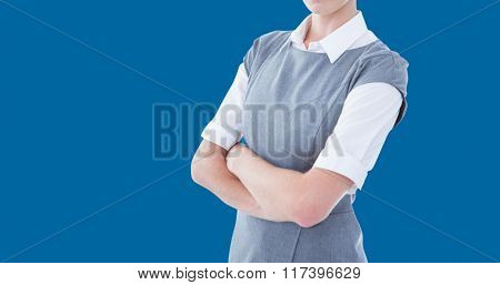 Portrait of serious businesswoman standing arms crossed against blue background