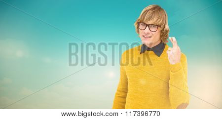 Portrait of hipster crossing his fingers against blue green background