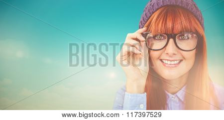 Smiling hipster woman looking at camera against blue green background