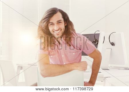 Portrait of hipster smiling while sitting on chair against computers and headsets