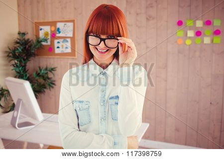 Portrait of a hipster woman front of post-it against creative office with cool wooden paneling