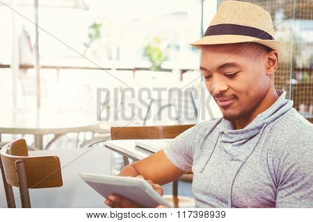 Composite image of smiling man using tablet