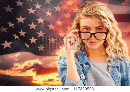 Portrait of businesswoman wearing eyeglasses posing against composite image of united states of america flag
