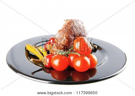 beef meat medallion with  tomatoes on black plate