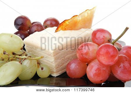 different type of grapes and cream cake on black