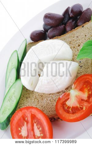 mozzarella on white plate with vegetables and bread