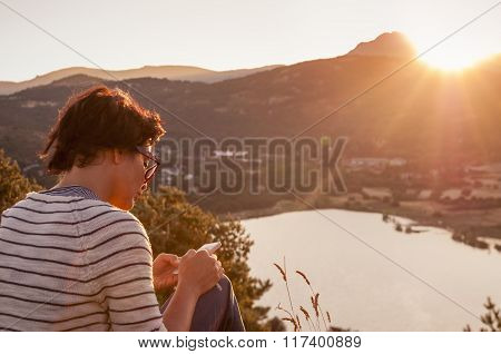 Young Woman Using Phone Device At Sunset