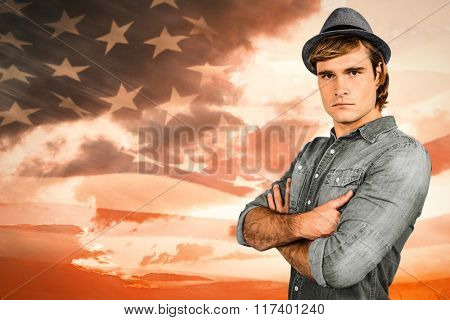 Serious hipster crossing his arms against composite image of digitally generated american flag rippling