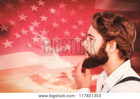Profile view of hipster touching beard against american flag rippling against sunrise over mountains