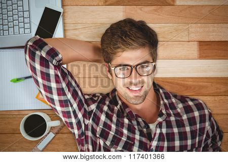 Hipster smiling while lying by laptop on hardwood floor against business desk with smartphone and laptop