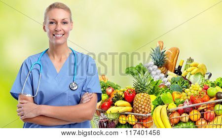 Smiling nurse near shopping cart with food.