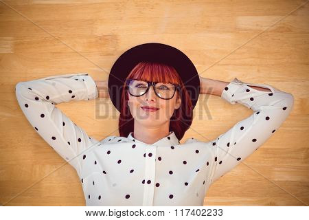 Attractive hipster woman lying on the floor against bleached wooden planks background