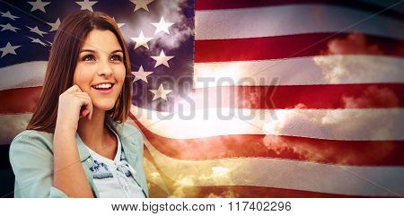 Smiling woman posing on white background against composite image of digitally generated united states national flag