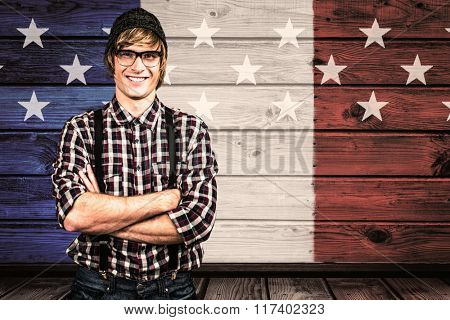 Smiling blond hipster crossing arms against composite image of usa national flag