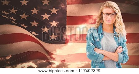 Portrait of businesswoman wearing eyeglasses with arms crossed against composite image of digitally generated united states national flag