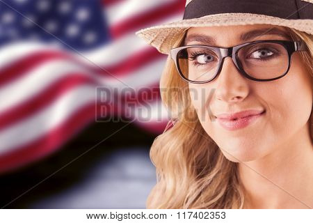 Gorgeous blonde hipster smiling against composite image of digitally generated united states national flag