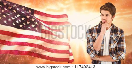 Confident businessman standing with hand on chin against composite image of lens flare