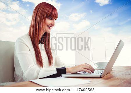 Smiling hipster businesswoman using her laptop against opening door in sky