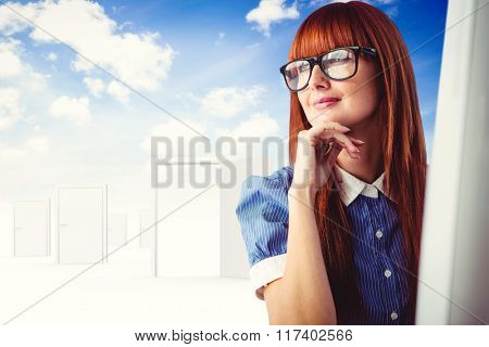 Attractive smiling hipster woman thinking against opening door in sky