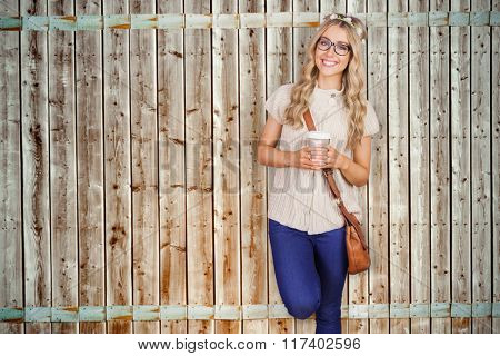 Gorgeous smiling blonde hipster leaning against red brick background against wooden background in pale wood