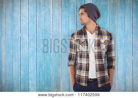 Confident hipster looking away while standing against wooden planks