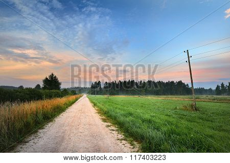 Sunrise At The Field With A Rural Road