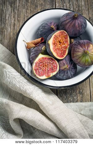 Ripe, juicy figs in bowl on textured wooden background
