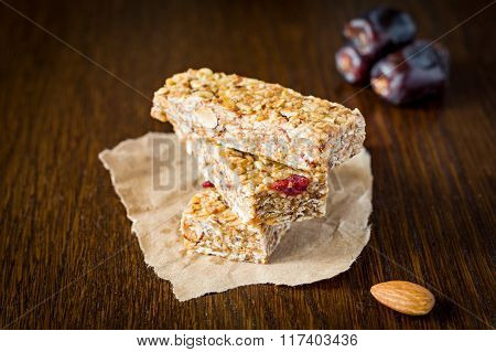 Granola bar or energy bar with oats, dates and nuts on brown wooden background