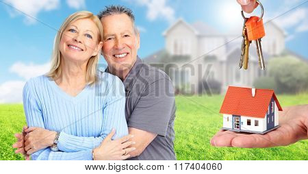 Happy senior couple near family house.