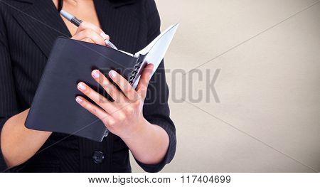Woman writing in a diary book.